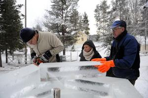 Torbjörn Persson sågar till ett isblock under överinseende av Charlotter Raaum och Arne Olsson.