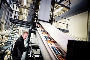"""Rutinerad. Stefan Sjölind har jobbat på tryckeriet V-tab Södertälje sedan 1983 och gjort det mesta. Han visar och berättar hur det går till när LT trycks. """"Här (läs: på plan tre i de så kallade trycktornen) är tidningssidorna färdigtryckta. Där borta vänds pappret och på vägen ner viks, häftas och klipps tidningen till rätt format"""", förklarar han."""