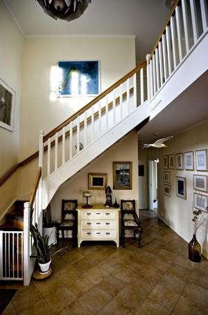 Rymd. Ljuset flödar in i båda våningsplanen från fönstret över ytterdörren. På väggen hänger en rad ramade planritningar, kopierade från lantmäteriet, som berättar skogsfastighetens historia.