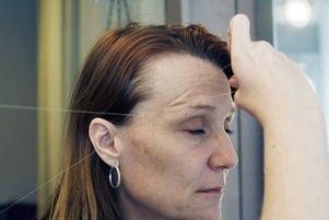 Hon trycker och drar med en speciell teknik så att hårstråna fastnar mellan de tvinnade trådarna.