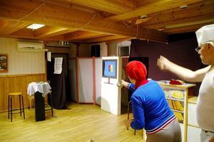 FJÄRRSTYRT. Inga Jönsson försöker få igång datorn av märket Appelskrutt med hjälp av fjärrkontrollen. På bilden syns även Föreståndarn, spelad av Örjan Kjetselberg.