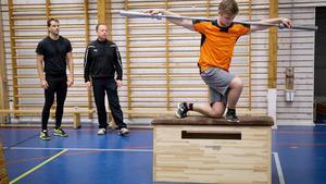 Fredrik Andersson tränar i Igelstavikens gymnastikhall under överinseende av Gabriel Wallin och Kari Kiviniemi.