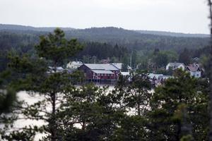 Sjöbodarna i Mellanfjärden skymtar fram genom träden.