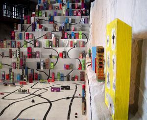 230 färgglada hus klär väggarna i Vitas vita värld, en värld framimproviserad av Sara Lundberg. Verket bottnar i Lundbergs böcker om Vita och i ett samarbete med 230 barn i Avesta.