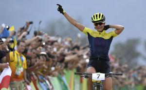 Sveriges Jenny Rissveds tar emot publikens hyllningar på upploppet på väg mot guldet i  damernas final i mountainbike.