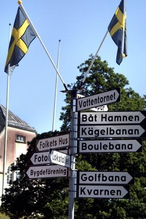 """Välskyltat. Över den vackra blomsterrundeln på """"torget"""" visar skyltar allt sevärt som finns i Åmmeberg och dess närhet."""