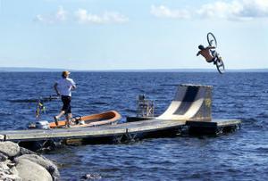 Thomas Liepecki flyger med sin cykel ut över rampen och ner i vattnet.