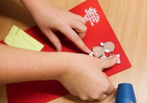 Jannice Kindsjö visa hur man gör ett eget julkort. Först stämplar hon och lägger på ett vitt pulver. Därefter använder hon en distanskudde för att lyfta figurerna från kortet.Det tar ungefär en halvtimme att skapa ett vackert kort.
