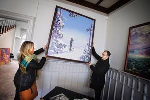 """Inlånad till utställningen. """"Han målade mycket hav och landskap"""", berättar Marja Skånberg och håller tillsammans med sin bror Gudmund Ingwall upp en av pappa Ulf Ingwalls målningar som är privatägd men som de lånat in till minnesutställningen."""