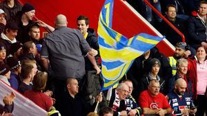 Christofer Blid bland fansen på ståplatsläktaren, till vänster om den gulblå flaggan.