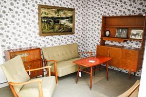 I ett traditionellt inrett vardagsrum i de egnahem får besökaren information om egnahemsrörelsen och villkoren för lånen. Tavlan på väggen är målad av en av sönerna till Olof Engberg.