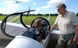 Pekka Havbrandt hjälper Daniel Ahlin att spänna fast sig i flygplanet.