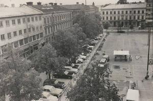 Så här såg Stortorgets västra del ut så sent som 1971. Norra Skeppargatan är obruten ända från ån upp till Valbogatan och utgör Stortorgets västligaste del. Den klassiska biografen Saga skymtar bakom allén och bilparkeringen.