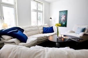 Plats för häng. Rummet rymmer förutom köksdelen en stor soffa och rejäla fåtöljer.