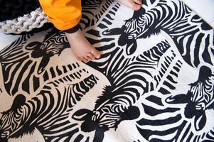 Små söta fötter på en skön zebramatta.