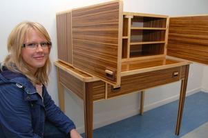 Marie Persson visar sitt skåp och sitt bord på utställningen i Mora.