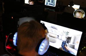 Hörlurar med blått ljus glimmar överallt i lokalen. Det är tyst, med fullt fokus på skärmarna. Snart börjar turneringen i spelet Counterstrike: Global offensive.