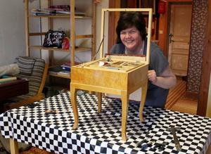 Anna-Lena Löfgren håller på att renovera en gammal pall med inbyggd sybehörslåda.