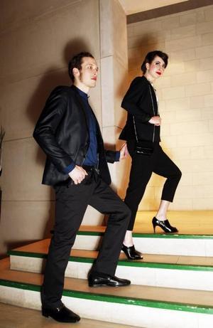 Tomas har en kavaj i metallicskimrande material, med blanka svarta band längs kavajslaget, 599 kr från H&M. Till det en djupblå skjorta med sotarkrage och svarta knappar, 299 kr från Åhléns., och ett par kostymbyxor i mörk granit och lätt strukturerade, 299 kr från H&M. Loafersinspirerade skor, 999 kr från Scorett. Malin har en kostym med haremskärning och hög midja på byxorna och kort kavaj, 349 kr respektive 499 kr, från Åhléns. Ett vitt linne med tryck ger en lite ledigare och festligare känsla, 129 kr från Åhléns. Halsbanden, 149 kr för pärlorna och 129 kr för kedjorna, båda från Lindex. En svart liten lackväska, 149 kr från Åhléns, och svarta skor, 599, kr från Scorett.