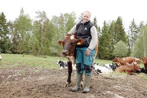 Frida Olsson, med kossan Trolli, vill fortsätta livet som mjölkbonde på Öster Grytinge gård, trots de ibland dystra prognoserna för svenskt lantbruk.