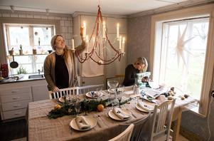 """""""Det är ett riktigt Cajsa Warg-hus med en massa udda saker. Och allt är snett och vint, men det är bara härligt"""", säger Maria (t.h.). Ljuskronan har systrarna prytt med trådar av rönnbär, som är enkla att göra själv hemma. Överlag är bär och kvistar från skogen fint att pynta med i jultider."""