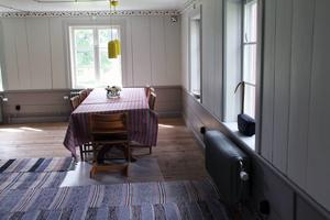Flera härliga trasmattor pryder de breda golvplankorna i matbordshörnan av det stora rummet.
