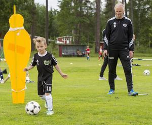 Eddie Käll dribblar med bollen under uppsyn av Ulf Lindström