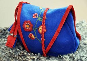 Väska i samiska färger med blommotiv.