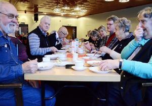 Glada miner vid gröttallrikarna. Håkan Persson, Maj-Britt Henriksson och de andra vid matbordet låter sig väl smaka.