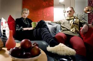 I soffan framför Ivanhoe är det nog många som spenderar nyårsdagen. Lisa och Royne är inget undantag. Lisa sitter i sina randiga långkalsonger från Vila, 159:95, och en stor pulloverliknande klänning från Fico för 1 399 kr. Under den har hon en skjortklänning med rutigt repmönster, 1 799 kr från Fico. Tofflor 450 kr, Scorett.Royne har en lång och varm tröja över sina hallonröda byxor, 999 kr respektive 1 199 kr, båda från Fico. Runt halsen en beige halsduk med svarta linjer, 899 kr från Fico.