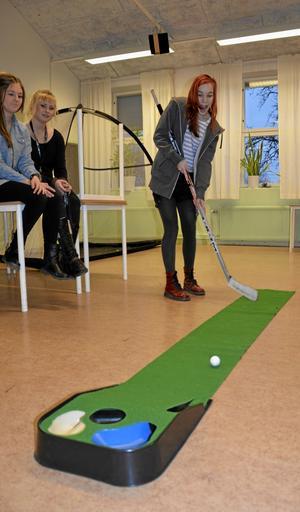 Minigolf modell Hällefors IK. Naomi Garnatz behärskar denna idrottsgren bra. Gymnasieeleverna Emma Lindgren och Sanna Holmström ser till att verksamheterna på öppet hus-dagen flyter på.