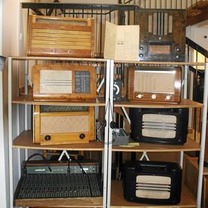 Efter ena väggen i studion finns gamla radioapparater som påminner om svunna tider i radiosammanhang.