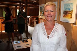 Konstnären och en av drivkrafterna bakom Hamnmagasinet, Helene Wallin, framför sina akvareller.