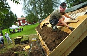 Många var nyfikna på Markus Gillbergs arbete med smedjans torvtak där näver och torv ser till att hålla byggnaden tät. Taket kommer att bli klart under augusti.