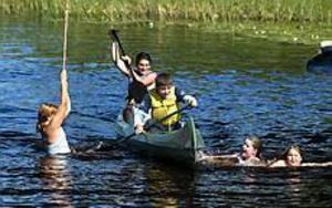 Foto: ANNAKARIN BJÖRNSTRÖM  Friluftsläger. När vattnet i Lundbosjön är 20 grader varmt ägnar sig de flesta barnen i Smörnäs åt bad eller kanotpaddling. I kanadensaren syns Zinan Allilali och Leif Bahd.