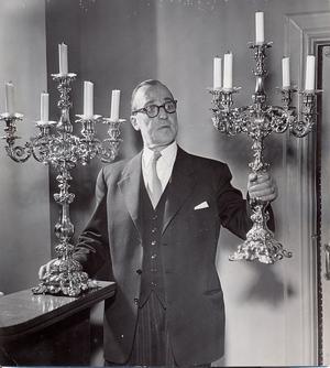 4 januari 1956. De två ståtliga kandelabrarna i antikt silver som hovmästare Harald Andersson visar på bilden känner många västeråsare igen. De 67 centimeter höga pjäserna hör till den festliga rekvisitan i Stadshotellets festvåning och har prytt upp bordet vid många bröllop och andra högtidliga tillfällen.