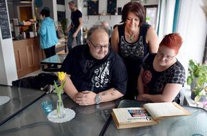 Per-Erik Persson, Tina Arvidson och Helen Jenerberg bläddrar i Tallbackens gamla gästbok och hoppas många vill vara med och blåsa liv i festplatsen.