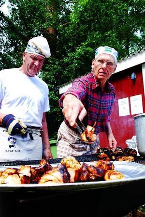 Folke Sundin och Rolf Sundström grillar spetten med nötkött, kassler och kyckling. Under våren har de lagat mat en gång i månaden tillsammans med tretton andra herrar, under ledning av kockstudenterna Per Martinsson och Stefan Gustafsson. Allt från pannbiff till raggmunk har det blivit: