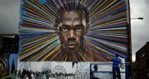 Gatuartisten James Cochran sprejar ett porträtt av den jamaicanska sportstjärnan Usain Bolt på en husvägg i östra London.