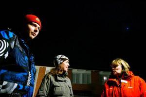 Nattvandraren Minda Kristiansen till höger med röd jacka pratar med några som lockats till torget.