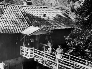I denna sagoskog finns endast en fast invånare, trädgårdsmästaren Elis Jonsson med familj. Hr Jonsson ses här med sin maka Elin på förstutrappan. Vid verandan fr v barnbarnen Roland och Henrik Toth samt kamraten Ingvar Sahlén, Västerås. Huset är ett f.d brygghus.