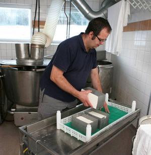 Att tillverka ost kräver en hel del jobb. Här vänder Jan Hammar ett antal ostar.