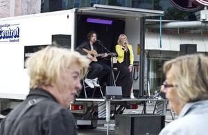 Hon sjunger ju riktigt bra. Troligen är det så damerna i förgrunden konstaterar när de överraskades av en minikonsert med Susanne Fellbrink på Stortorget under gårdagens lunchtimme.