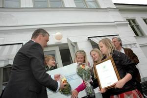 GRATTIS. Peter Kontturi ger en check på 10 000 kronor till elever på Sörgärdets skola i Älvkarleby. Skolan får priset för ett projekt om rörelse och konstruktion.