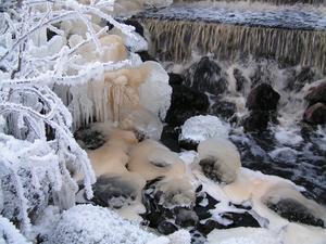 En vintrig bild på lilla vattenfallet vid sjön.