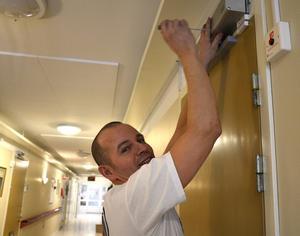 Egenföretagare Joakim Hallin monterar upp dörrstängare på lägenheternas dörrar.