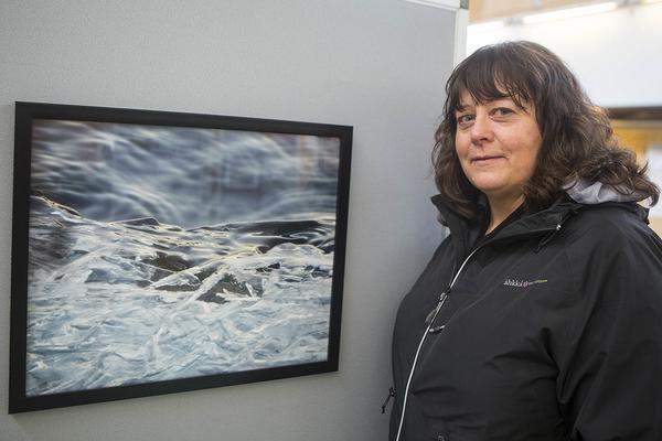 Nancy Persson vid en av sina bilder som nu hängt en månad i Ljushallen i Sveg.