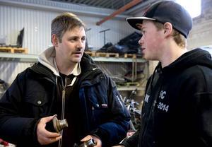 Fritidsledaren Jonas Sjödin hjälper Mattias Wikholm med växellådan till a-traktorn.