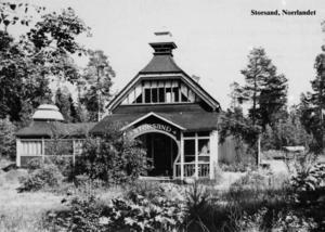 Storsands landställe började som ölpaviljong vid Gävleutställningen 1901 och köptes sen av Gävles missionsförening. Byggnaden fungerade som barnkoloni och gudstjänstlokal sommartid och P P Waldenström predikade där. På 1940-talet blev den privatägd och 1988 brann den. Åke Nylén tog fotot 1975 för Gävle Gilles årskort 1989.