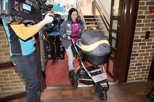 Marit Björgen på presskonferens med sonen Marius i vagnen. FIS vill försöka underlätta för henne och andra nyblivna mammor.
